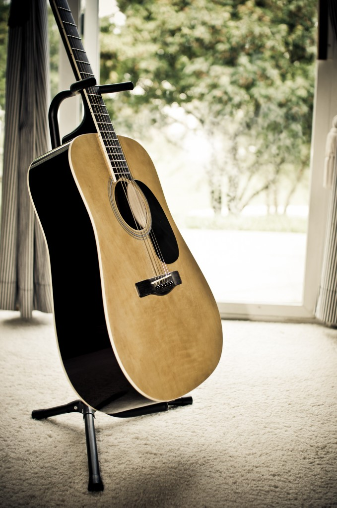 Acoustic guitar on a guitar stand Poway guitar lessons 619-306-3664